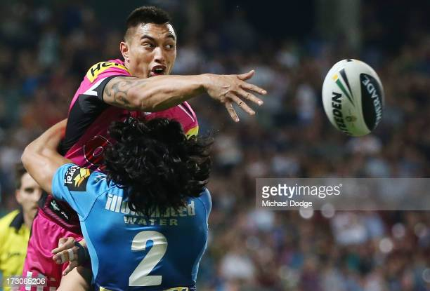 Dean Whare of the Panthers passes the ball while being tackled by Kevin Gordon of the Titans during the round 17 NRL match between the Gold Coast...