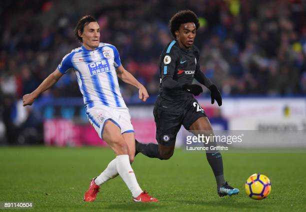 Dean Whitehead of Huddersfield Town passes the ball under pressure from Willian of Chelsea during the Premier League match between Huddersfield Town...