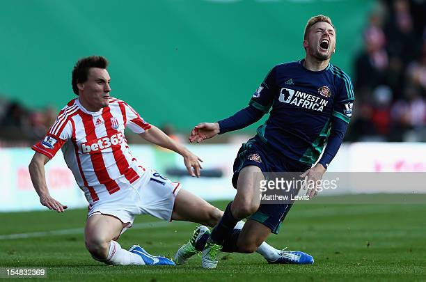 Dean Whitehead of Stoke tackles Sebastian Larsson of Sunderland during the Barclays Premier League match between Stoke City and Sunderland at...