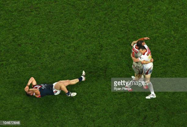 Dean Young and Brett Morris of the Dragons celebrate as Martin Kennedy of the Roosters looks dejected as the final siren sounds during the NRL Grand...