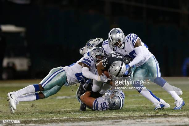 DeAndré Washington of the Oakland Raiders is tackled by Sean Lee Xavier Woods and Anthony Brown of the Dallas Cowboys at OaklandAlameda County...