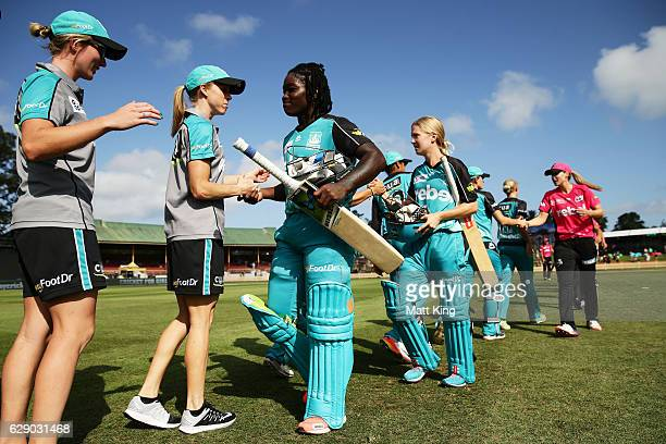 Deandra Dottin and Jemma Barsby of the Heat celebrate with team mates as they walk from the field after victory in the the Women's Big Bash League...