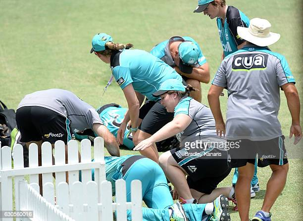 Deandra Dottin of the Heat and team mate Laura Harris are seen laying on the ground after colliding in the field during the WBBL match between the...