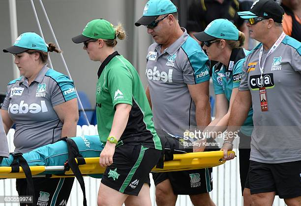 Deandra Dottin of the Heat is taken from the field injured after colliding in the field with team mate Laura Harris during the WBBL match between the...