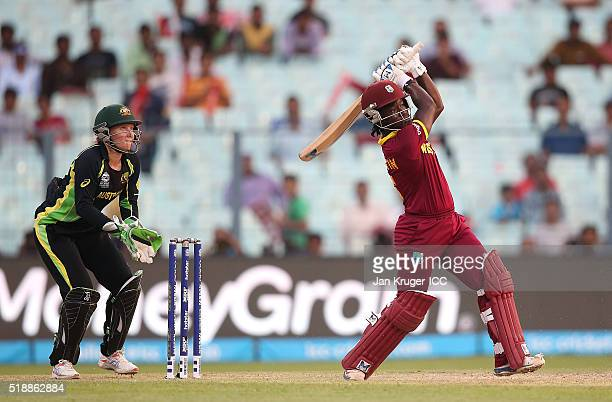 Deandra Dottin of the West Indies hits out with Alyssa Healy of Australia looking on during the Women's ICC World Twenty20 India 2016 final match...