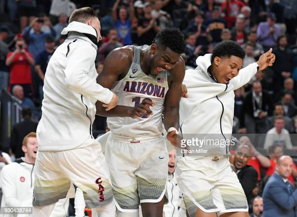Deandre Ayton of the Arizona Wildcats celebrates with teammates on the court after the team defeated the USC Trojans 7561 to win the championship...