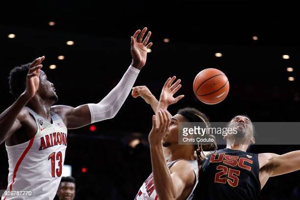 Deandre Ayton and Keanu Pinder of the Arizona Wildcats fight for a rebound with Bennie Boatwright of the USC Trojans during the second half of the...