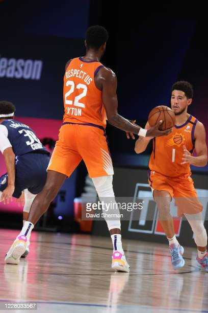 Deandre Ayton hands the ball off to teammate Devin Booker of the Phoenix Suns during the game against the Dallas Mavericks on August 13 2020 at...