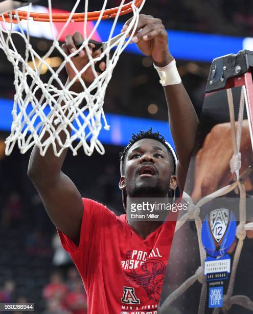 Deandre Ayton of the Arizona Wildcats cuts down a net after the team defeated the USC Trojans 7561 to win the championship game of the Pac12...