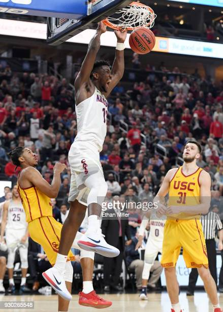 Deandre Ayton of the Arizona Wildcats dunks against Elijah Stewart and Nick Rakocevic of the USC Trojans during the championship game of the Pac12...