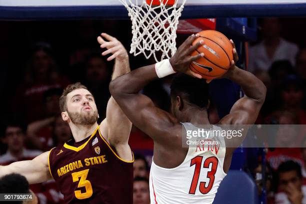 Deandre Ayton of the Arizona Wildcats grabs a rebound over Mickey Mitchell of the Arizona State Sun Devils during the second half of the college...