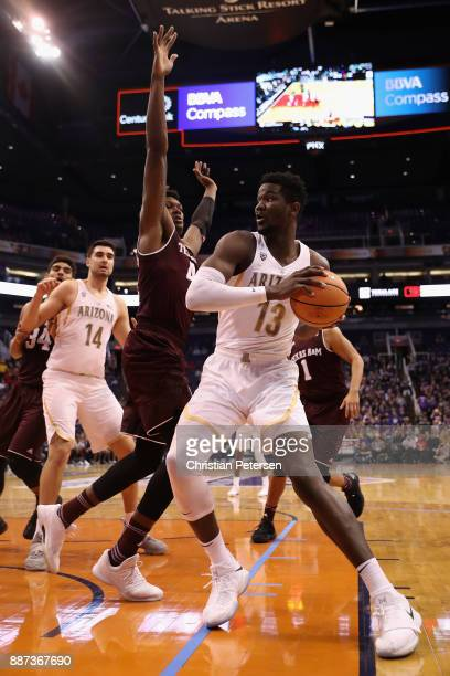 Deandre Ayton of the Arizona Wildcats looks to pass around Robert Williams of the Texas AM Aggies during the college basketball game at Talking Stick...