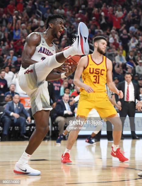 Deandre Ayton of the Arizona Wildcats reacts in front of Nick Rakocevic of the USC Trojans after dunking during the championship game of the Pac12...