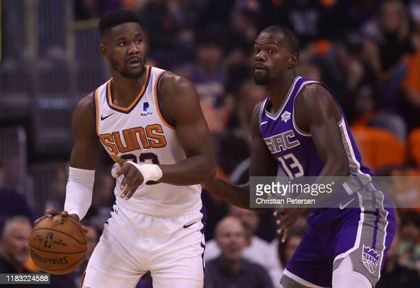Deandre Ayton of the Phoenix Suns handles the ball under pressure from Dewayne Dedmon of the Sacramento Kings during the first half of the NBA game...