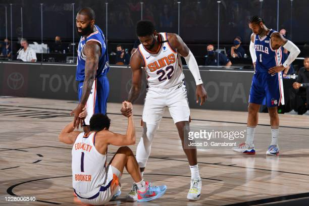 Deandre Ayton of the Phoenix Suns helps up Devin Booker of the Phoenix Suns during a game against the Philadelphia 76ers on August 11 2020 at Visa...