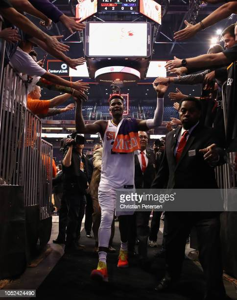 Deandre Ayton of the Phoenix Suns high fives fans as he walks off the court following the NBA game against the Dallas Mavericks at Talking Stick...