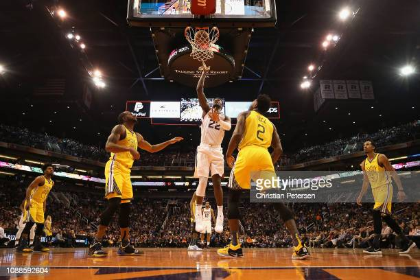Deandre Ayton of the Phoenix Suns laysup a shot over Jordan Bell of the Golden State Warriors during the second half of the NBA game at Talking Stick...