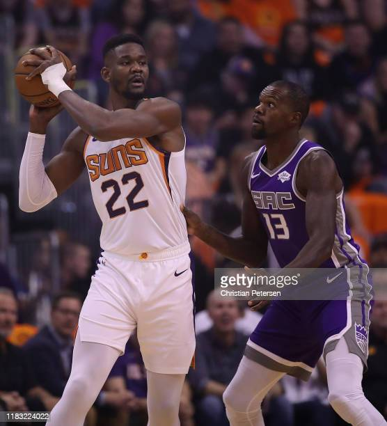 Deandre Ayton of the Phoenix Suns looks to pass under pressure from Dewayne Dedmon of the Sacramento Kings during the first half of the NBA game at...