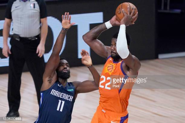 Deandre Ayton of the Phoenix Suns passes over Tim Hardaway Jr #11 of the Dallas Mavericks in the first half at AdventHealth Arena at ESPN Wide World...
