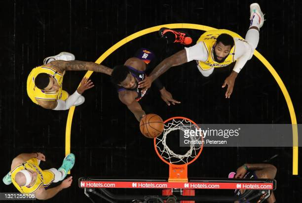 Deandre Ayton of the Phoenix Suns puts up a shot over Kyle Kuzma, Andre Drummond and Alex Caruso of the Los Angeles Lakers during the first half in...