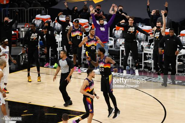 Deandre Ayton of the Phoenix Suns reacts alongside Devin Booker, Mikal Bridges and Torrey Craig after a slam dunk against the LA Clippers during the...