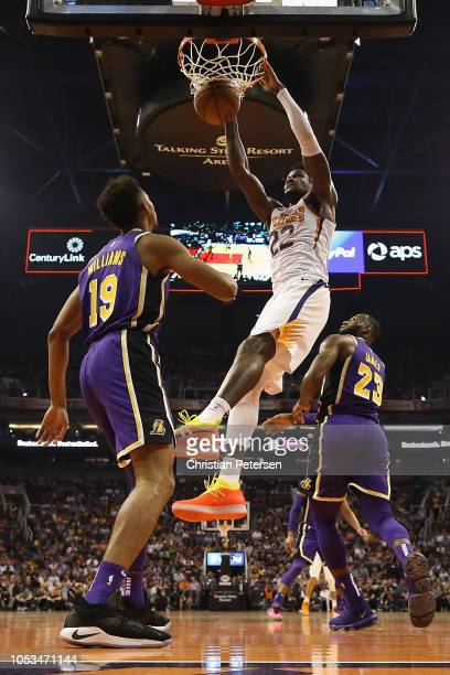 Deandre Ayton of the Phoenix Suns slam dunks the ball over Johnathan Williams and LeBron James of the Los Angeles Lakers during the NBA game at...