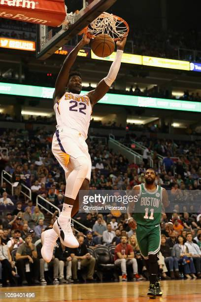 Deandre Ayton of the Phoenix Suns slam dunks the ball past Kyrie Irving of the Boston Celtics during the first half of the NBA game at Talking Stick...