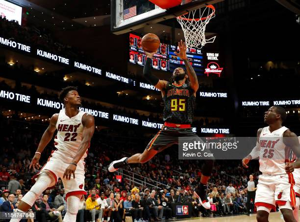 DeAndre' Bembry of the Atlanta Hawks drives against Jimmy Butler and Kendrick Nunn of the Miami Heat in the second half at State Farm Arena on...