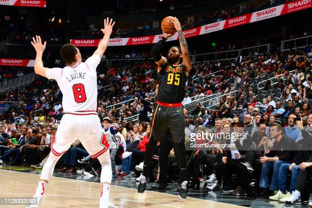 DeAndre' Bembry of the Atlanta Hawks shoots corner three over Zach LaVine of the Chicago Bulls on March 1 2019 at State Farm Arena in Atlanta Georgia...