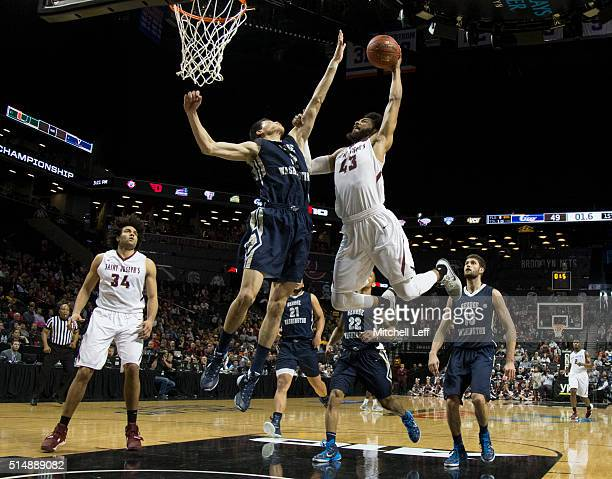DeAndre Bembry of the Saint Joseph's Hawks attempts a dunk against Yuta Watanabe of the George Washington Colonials in the quarterfinals round of the...