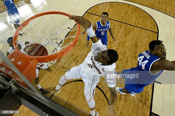 DeAndre Daniels of the Connecticut Huskies dunks as Dakari Johnson of the Kentucky Wildcats defends during the NCAA Men's Final Four Championship at...