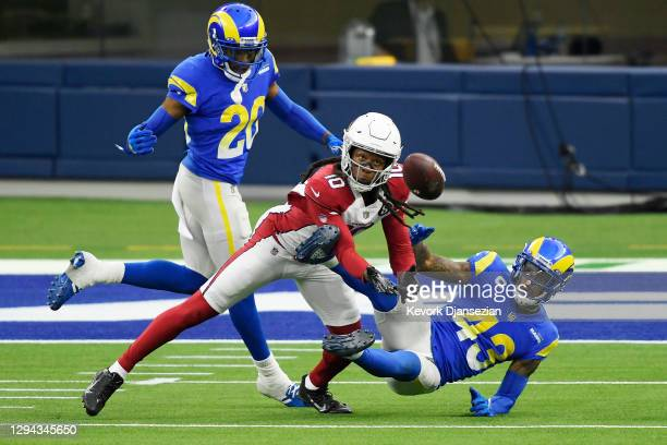 DeAndre Hopkins of the Arizona Cardinals makes a reception as he is defended by Jalen Ramsey and John Johnson III of the Los Angeles Rams during the...