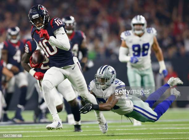 DeAndre Hopkins of the Houston Texans breaks the tackle of Byron Jones of the Dallas Cowboys in the first quarter at NRG Stadium on October 7 2018 in...