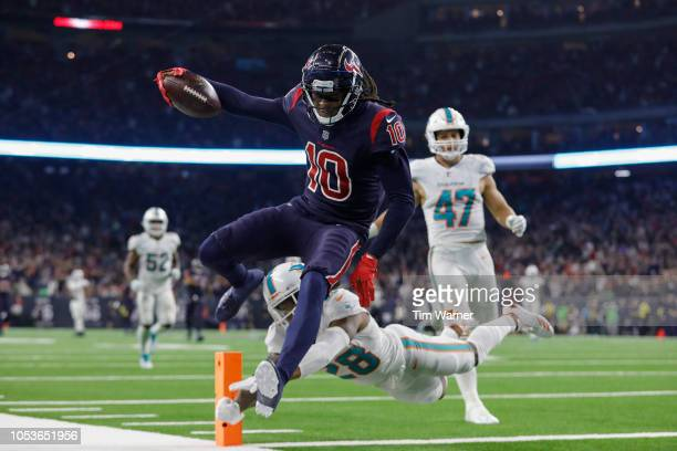 DeAndre Hopkins of the Houston Texans catches a pass and runs for a touchdown in the fourth quarter defended by Bobby McCain of the Miami Dolphins at...