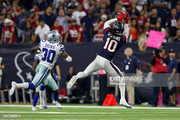 DeAndre Hopkins of the Houston Texans catches a pass in overtime defended by Anthony Brown of the Dallas Cowboys at NRG Stadium on October 7 2018 in...