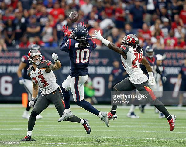 DeAndre Hopkins of the Houston Texans completes a reception as Chris Conte of the Tampa Bay Buccaneers and Mike Jenkins defend at NRG Stadium on...