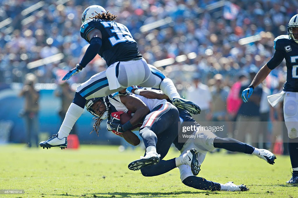 DeAndre Hopkins #10 of the Houston Texans is tackled by Blidi Wreh-Wilson #25 and Daimion Stafford #39 of the Tennessee Titans at LP Field on October 26, 2014 in Nashville, Tennessee. The Texans defeated the Titans 30-16.