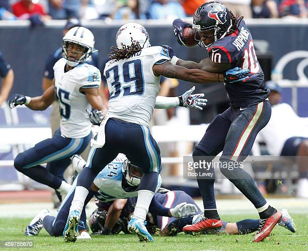 DeAndre Hopkins of the Houston Texans is tackled by Daimion Stafford of the Tennessee Titans in the fourth quarter in a NFL game on November 30 2014...
