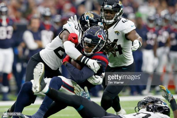 DeAndre Hopkins of the Houston Texans is tackled by D.J. Hayden of the Jacksonville Jaguars and Myles Jack in the second quarter at NRG Stadium on...
