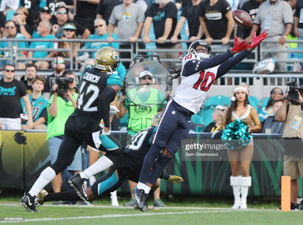 DeAndre Hopkins #10 of the Houston Texans reaches for the football in front of Jalen Ramsey #20 and Barry Church #42 of the Jacksonville Jaguars during the second half of their game at EverBank Field on December 17, 2017 in Jacksonville, Florida.