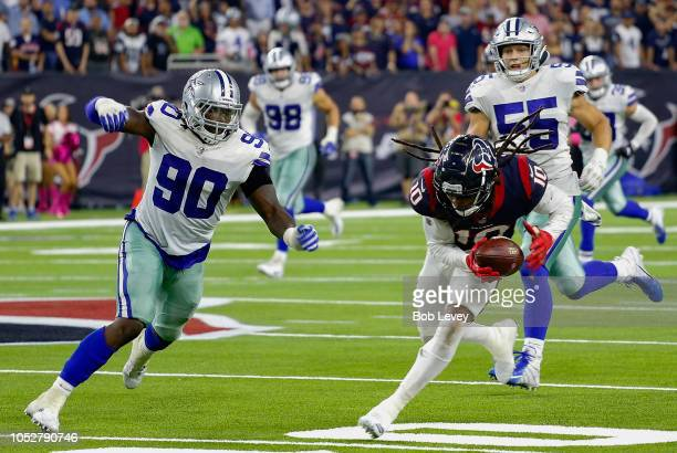DeAndre Hopkins of the Houston Texans runs with the ball after a catch as Demarcus Lawrence of the Dallas Cowboys and Leighton Vander Esch pursue at...