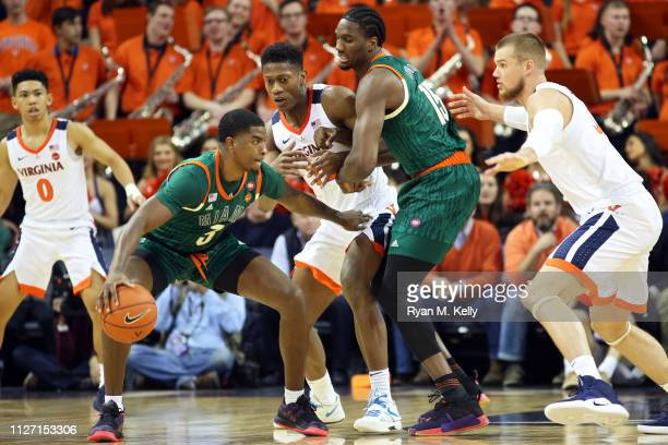De'Andre Hunter and Jack Salt of the Virginia Cavaliers defend Anthony Lawrence II and Ebuka Izundu of the Miami Hurricanes in the second half during...