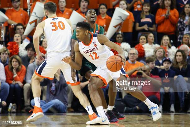 De'Andre Hunter drives to the basket as Jay Huff of the Virginia Cavaliers sets a pick on Anthony Lawrence II of the Miami Hurricanes in the first...