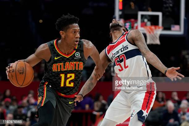 De'Andre Hunter of the Atlanta Hawks dribbles past Jordan McRae of the Washington Wizards in the first half at Capital One Arena on January 10 2020...