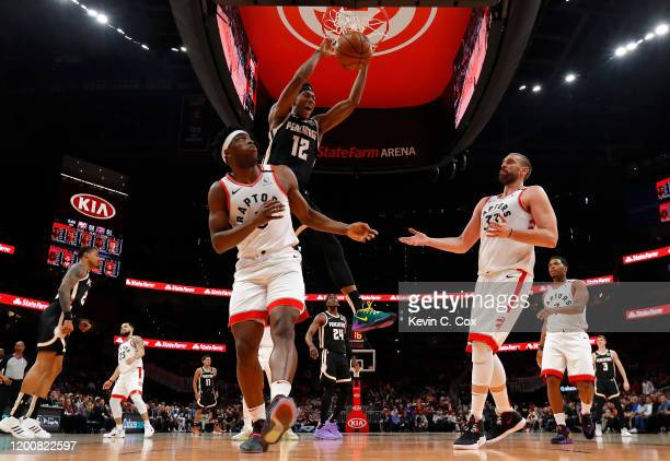 De'Andre Hunter of the Atlanta Hawks dunks against OG Anunoby Marc Gasol of the Toronto Raptors in the first half at State Farm Arena on January 20,...