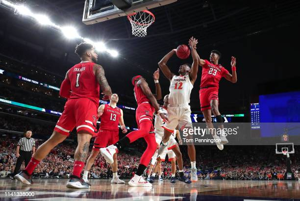 De'Andre Hunter of the Virginia Cavaliers attempts a shot against Tariq Owens and Jarrett Culver of the Texas Tech Red Raiders in the first half...