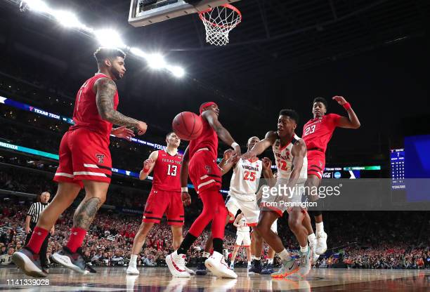 De'Andre Hunter of the Virginia Cavaliers attempts a shot against Tariq Owens and Jarrett Culver of the Texas Tech Red Raiders during the 2019 NCAA...