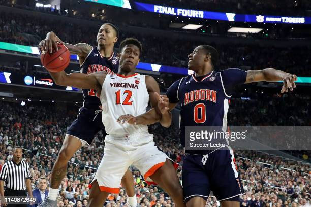 De'Andre Hunter of the Virginia Cavaliers battles for the ball with J'Von McCormick and Horace Spencer of the Auburn Tigers in the second half during...