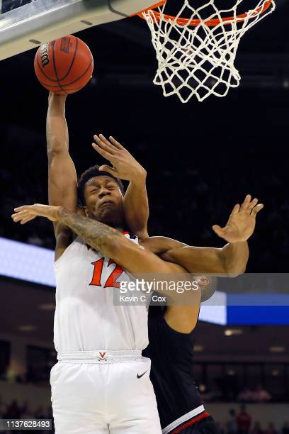De'Andre Hunter of the Virginia Cavaliers drives to the basket against Brandon Miller of the Gardner Webb Runnin Bulldogs in the second half during...