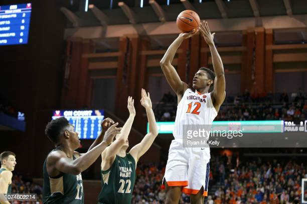 De'Andre Hunter of the Virginia Cavaliers shoots over Paul Rowley and Nathan Knight of the William Mary Tribe in the second half during a game at...